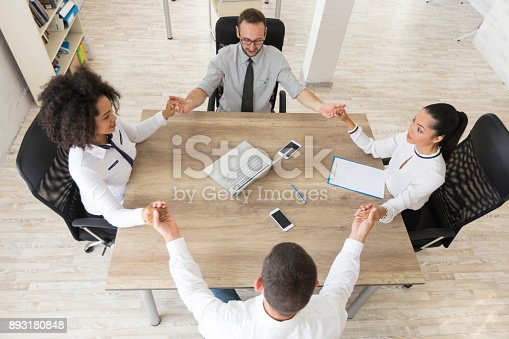 1016771914 istock photo Team of young people holding hands in modern workplace 893180848