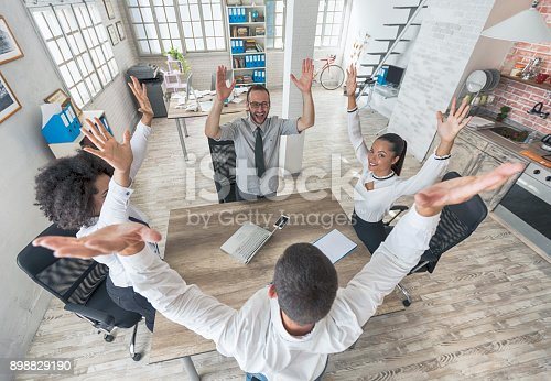 1016771914 istock photo Team of young people holding hands in modern workplace 898829190