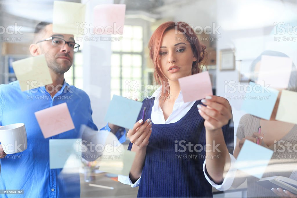 Team of young people using reminders at work stock photo