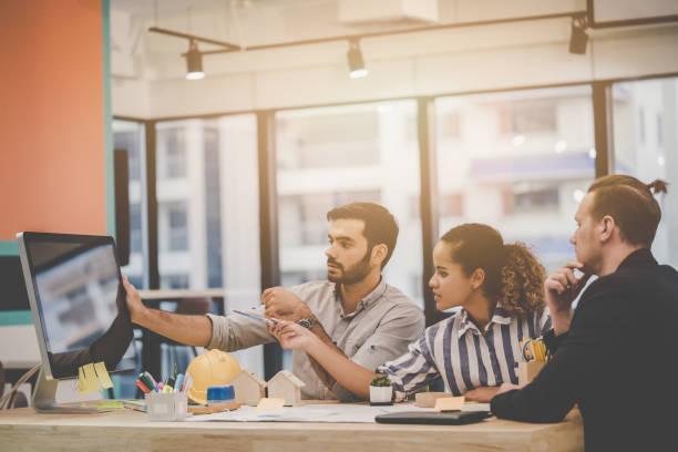 Equipo de jóvenes contratistas de bienes raíces desarrollador de la casa está haciendo una lluvia de ideas en la oficina. Tres personas de negocios modernas es la discusión en una reunión para el éxito empresarial. - foto de stock