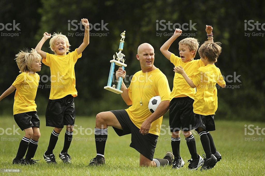 Team Of Young Soccer Players Celebrating Victory On Field royalty-free stock photo
