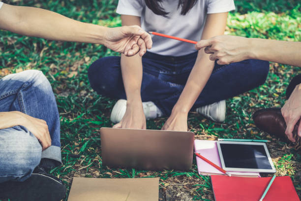 Team of young students studying in a group project in the park of university or school. Happy learning, community teamwork and youth friendship concept. Team of young students studying in a group project in the park of university or school. Happy learning, community teamwork and youth friendship concept. borrowing stock pictures, royalty-free photos & images