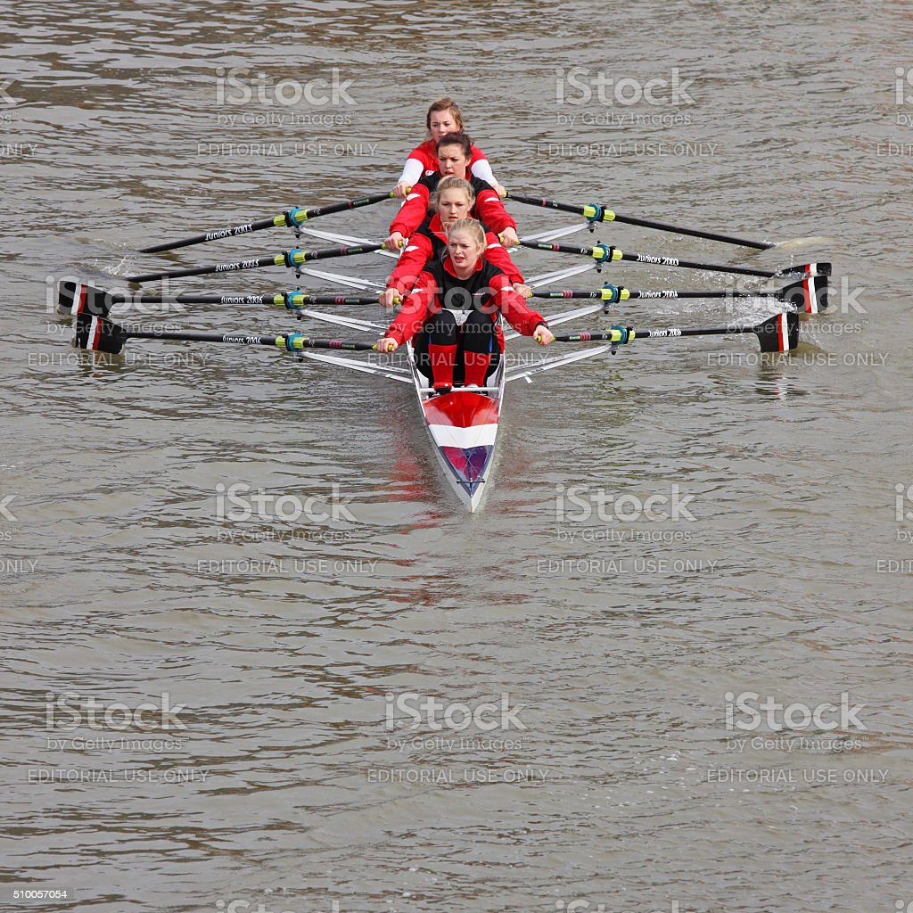 Team of young women rowing to a race start point stock photo