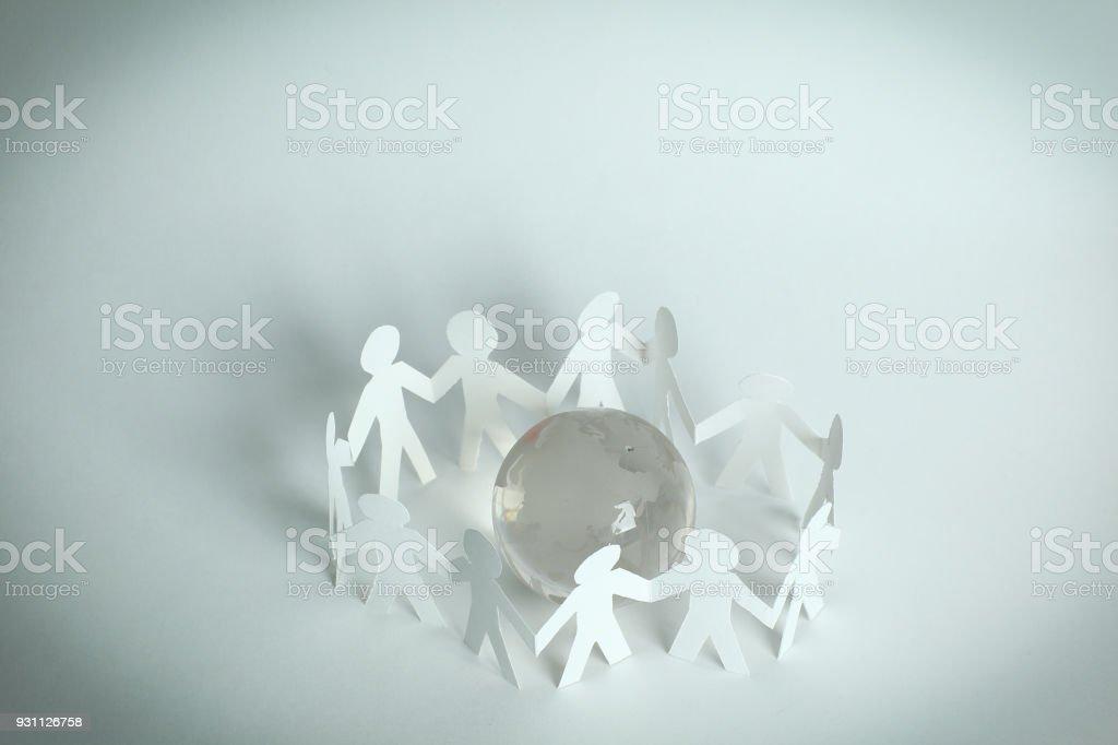 team paper men standing around the glass globe stock photo