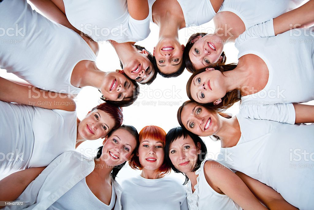 Team Group of women standing in the circle, smiling at the camera against white background. Low angle view. Adult Stock Photo
