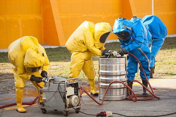 HAZMAT team HAZMAT team, coolecting dangerous materials, working with pump. hazardous chemicals stock pictures, royalty-free photos & images