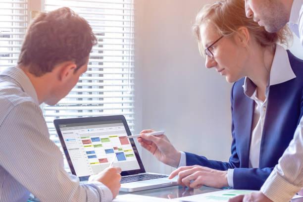 Sie planen ein Meeting mit Kalender auf Computer, Suche Zeitfenster zwischen Termine, Aufgaben und Termine, geschäftige Menschen Arbeit, Kollegen im Büro organisieren mit Zeitmanagement Tool Team – Foto