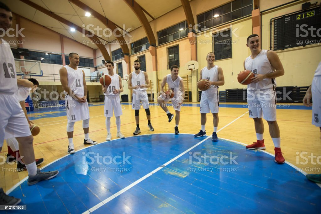 Basketball players standing together and holding basket balls