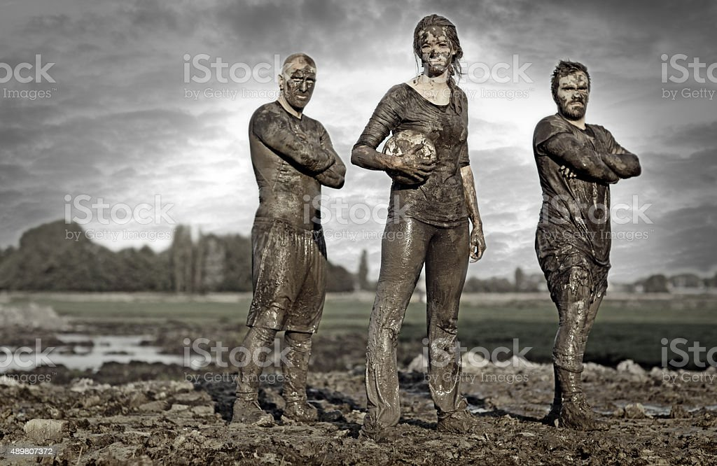 Team posing for a group pic in the mud stock photo