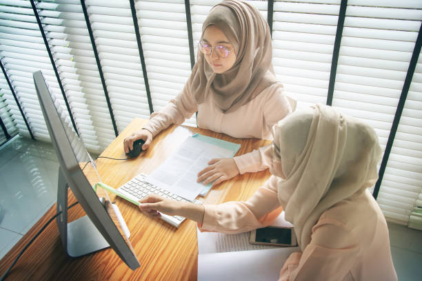 Proyecto de equipo en el trabajo de estudiantes musulmanes asiáticos. - foto de stock