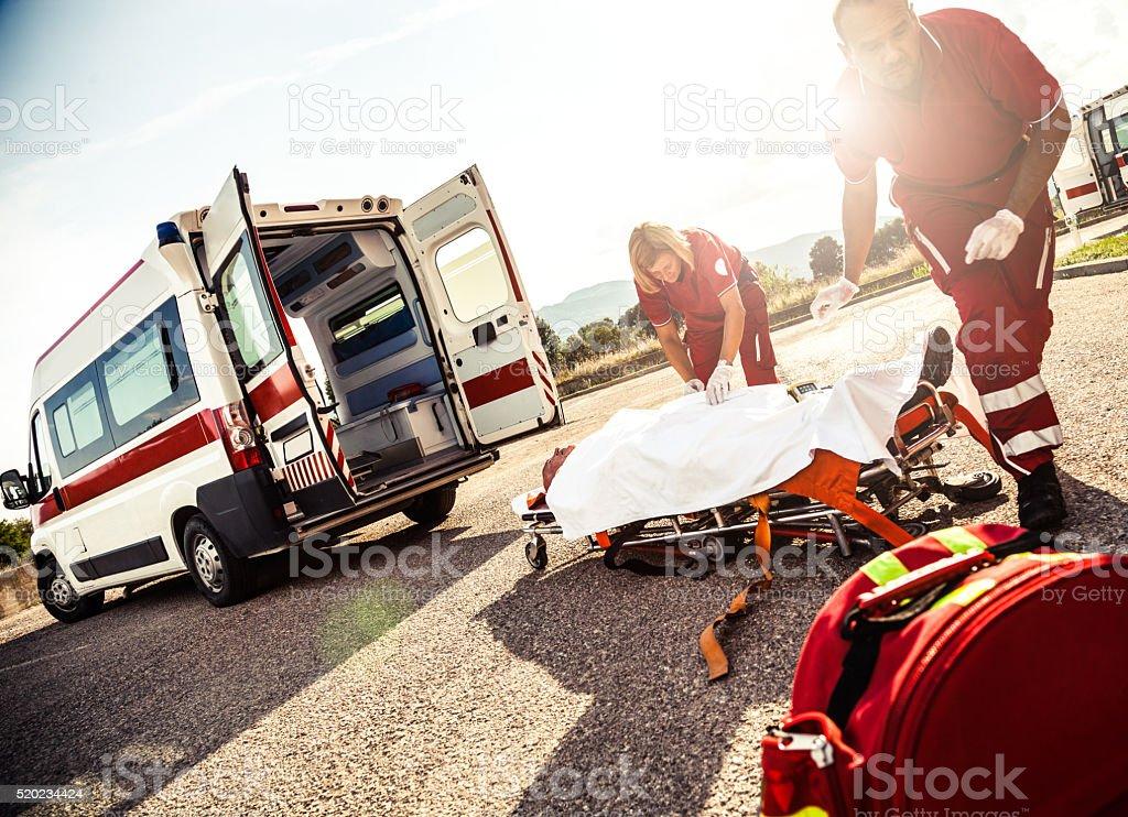 EMT team fornire primo soccorso su strada - foto stock