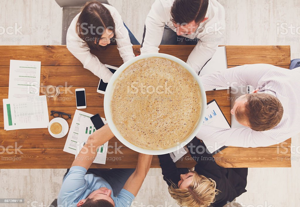 Team put hands together holding giantic cup of coffee stock photo