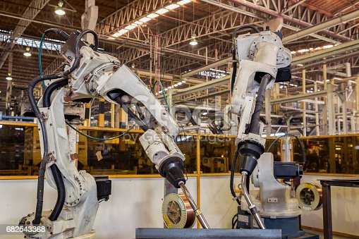 istock Team robots are welding assembly automotive part in factory 682543368