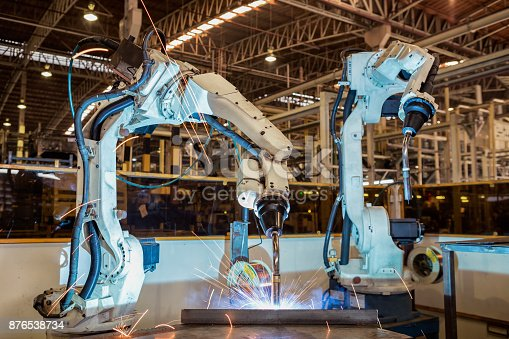 114166156 istock photo Team robots are welding assembly part in car factory 876538734