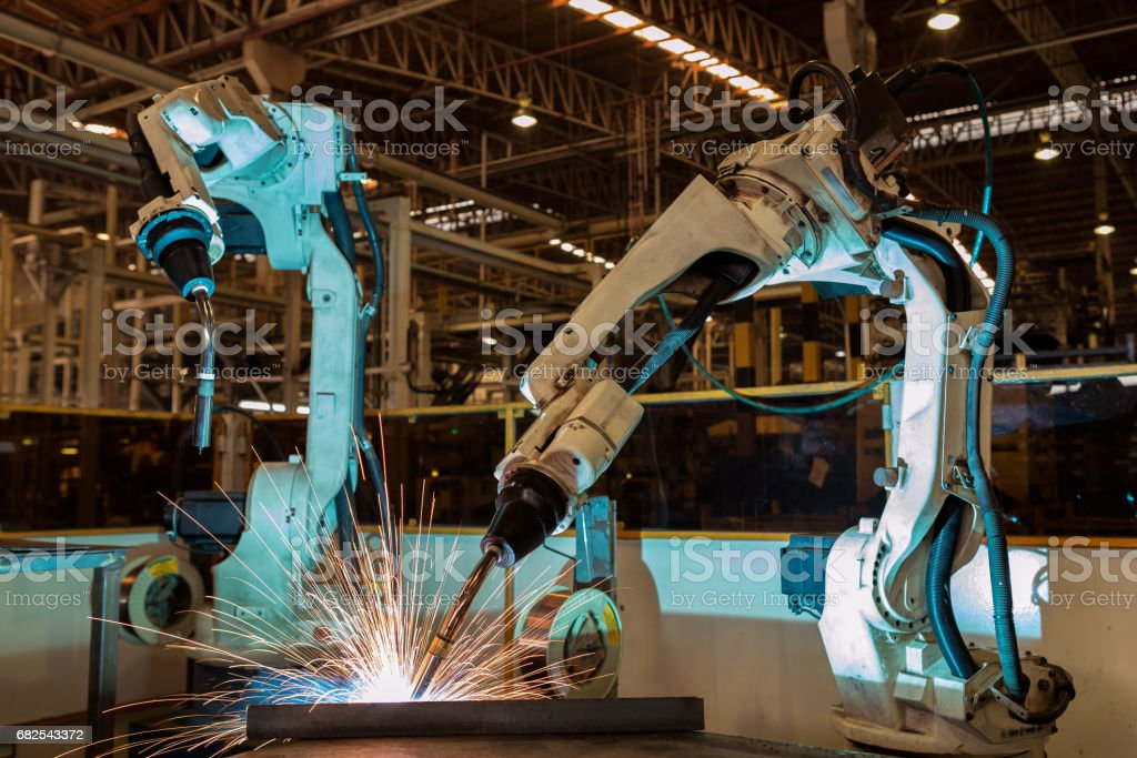 Team robots are welding assembly  part in factory stock photo