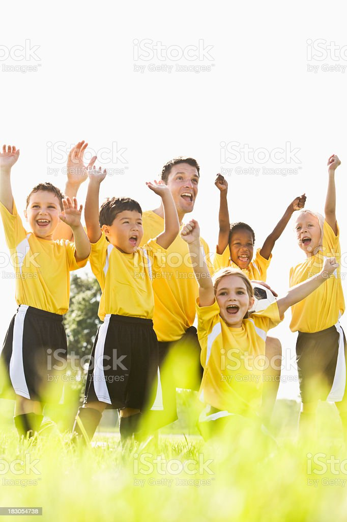 Team spirit, happy young soccer kids with coach cheering victory royalty-free stock photo