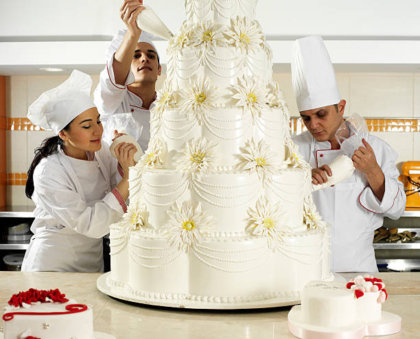 Team spirit in pastry 3 chef completing wedding cake. decorating a cake stock pictures, royalty-free photos & images