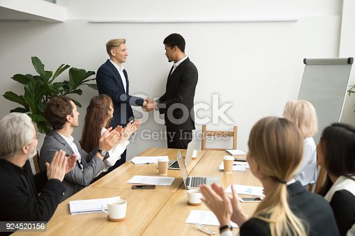 923041456 istock photo Team supporting applauding black ceo and white employee shaking hands 924520156