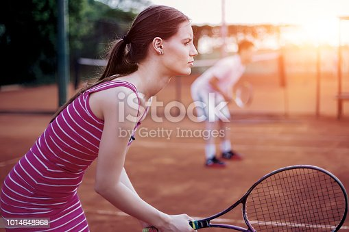 Couple Playing Doubles at the Tennis Court. Healthy Lifestyle Concept