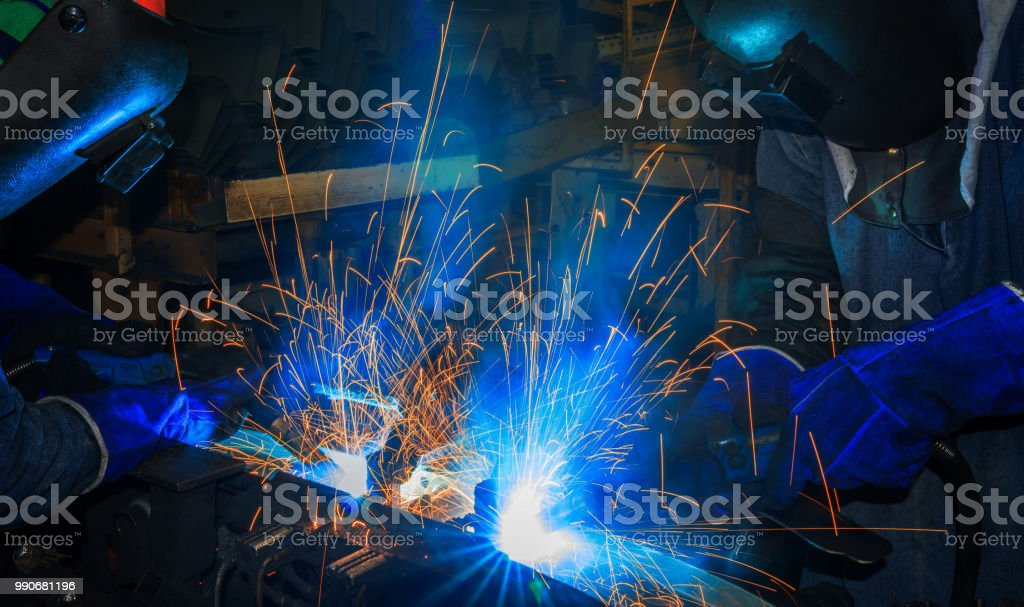Team welders are welding merging metal part in factory stock photo