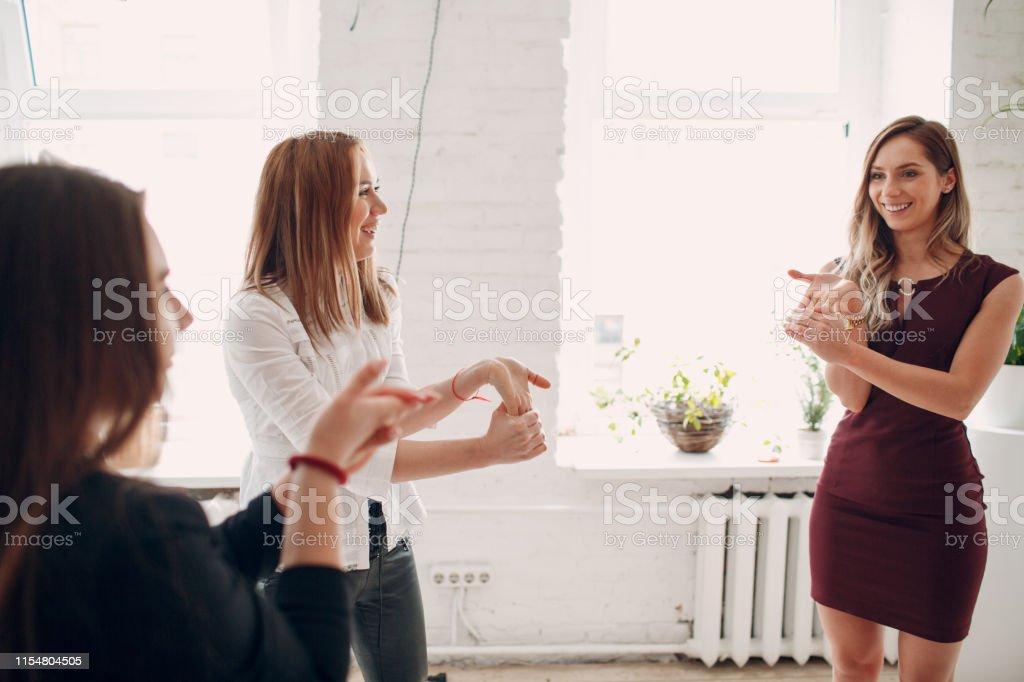 Team women doing exercises in office. Exercising females at work....
