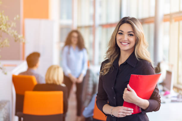 Team work discussing. Young woman with paper folder. Team work discussing. Open space office and startup crew brainstorming at new project. Young woman with paper folder. Film effect, blurry background, lens flare effect. bureaucracy stock pictures, royalty-free photos & images