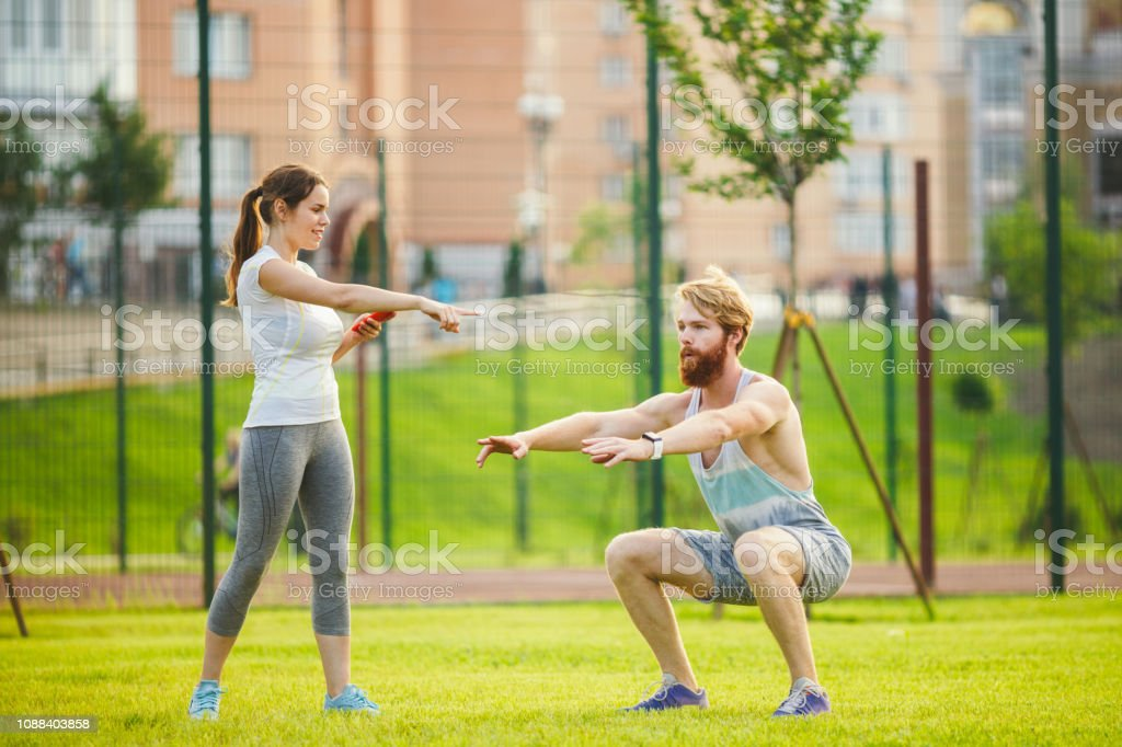 Team work in sports. female trainer training man with beard in park...