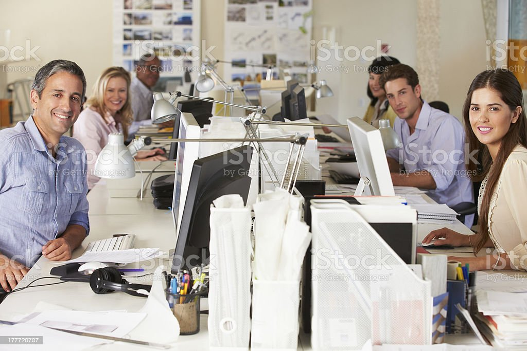 Team Working At Desks In Busy Office stock photo