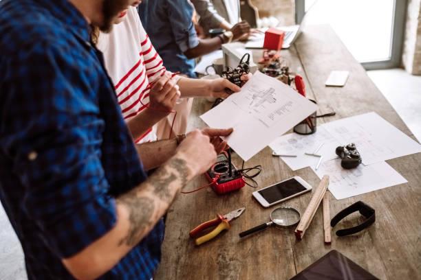 teamarbeit auf neuen rechner - grafik design tattoos stock-fotos und bilder