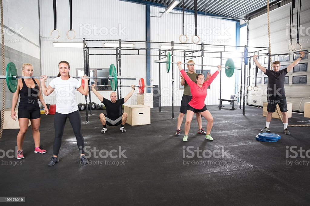 Team workout with weights at fitness gym center stock photo