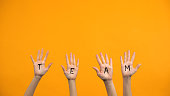 istock Team written palms on orange background, unity cooperation, group togetherness 1176426452
