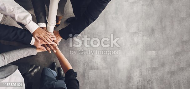 Teambuilding concept. Business team putting their hands together, top view, free space, panorama