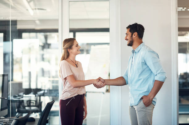 Teaming up to take their business places Shot of a businessman and businesswoman shaking hands in a modern office design occupation stock pictures, royalty-free photos & images