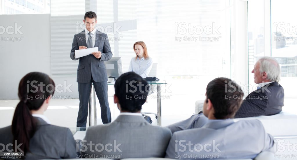 A teamleader talking to his colleagues stock photo