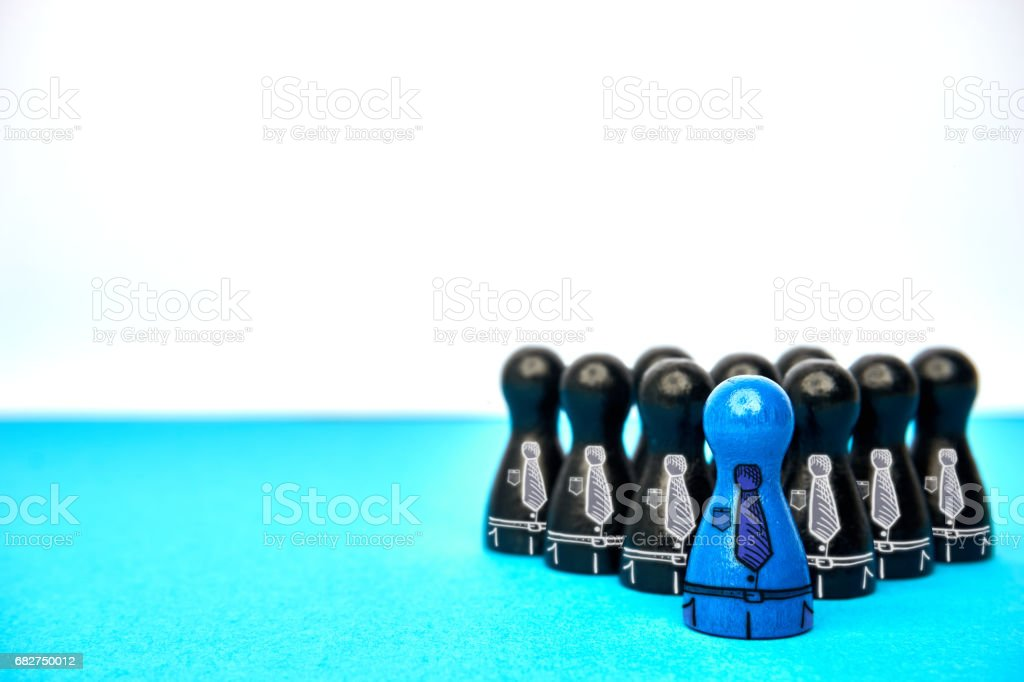 Teamleader with his team - with copyspace. Symbol for leadership with game figures in blue and black and drawn suit elements. stock photo