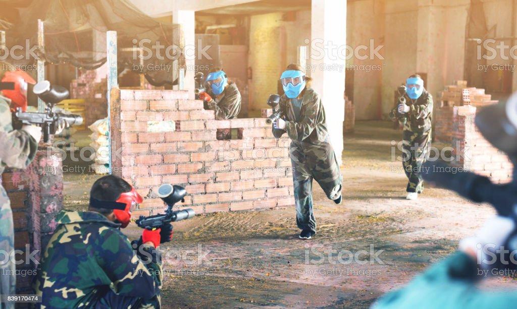 Equipes enfrentadas-se no campo de batalha na arena de paintball. - foto de acervo
