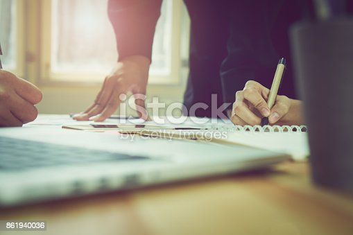 istock teamwork, A man's hand pointing to a graph of financial graphs to inform his colleagues of the numbers. laptop on table used to calculate the correct. 861940036