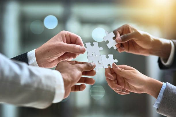 teamwork, a sure solution to a business challenge - puzzles stock photos and pictures