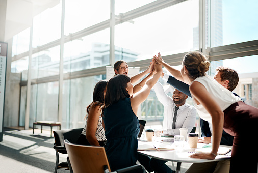 Shot of a group of businesspeople high fiving while sitting in a meeting