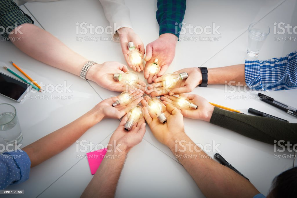 Teamwork and brainstorming concept with businessmen that share an idea with a lamp. Concept of startup stock photo