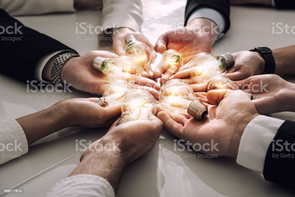 Teamwork and brainstorming concept with businessmen that share an idea with a lamp. Concept of startup foto stock royalty-free