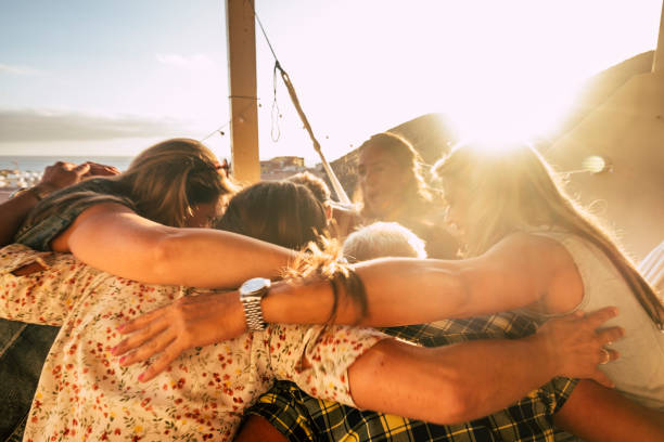 Teamwork and friendship concept for people outdoor hugging all together with love and friends lifestyle - happiness and relationship with group of females having fun - ocean view stock photo