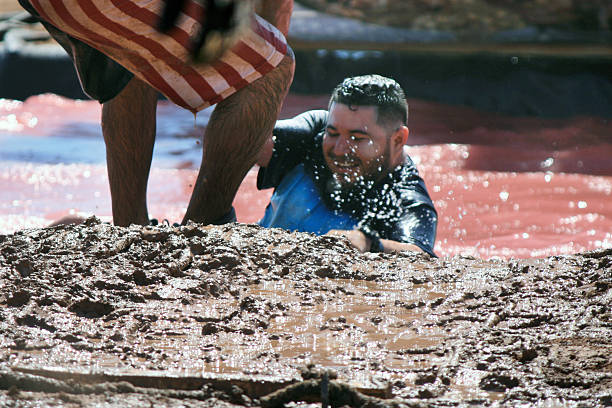 teamwork at mud run event A man helps his friend up a muddy bank during a mud run obstacle course event mud run stock pictures, royalty-free photos & images