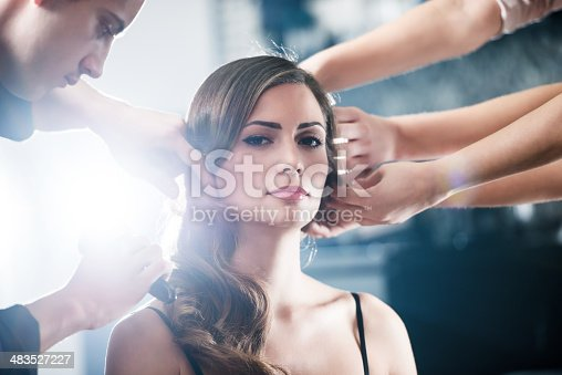 Team of fashion stylist making a retro hairstyle to their customer.