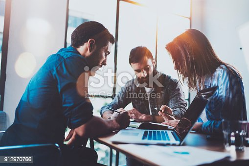912969272istockphoto Teamwork brainstorming process.Young man working together with partners in modern office loft.Business startup concept.Blurred background.Flares.Cropped. 912970766