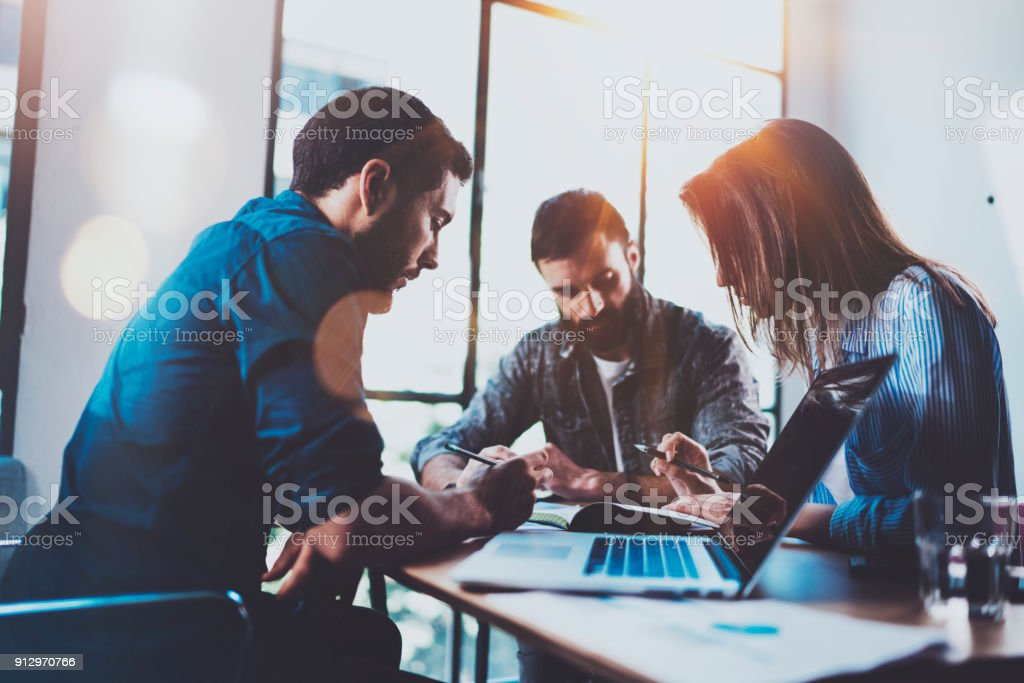 Teamwork brainstorming process.Young man working together with partners in modern office loft.Business startup concept.Blurred background.Flares.Cropped. stock photo