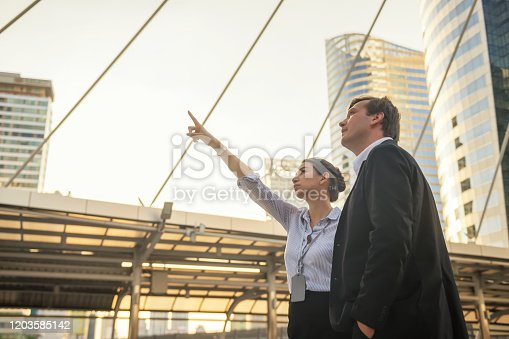 Female worker point finger to modern building  with her American businessman boss to discuss business construction investment project with sunset light. Real estate investment industry.