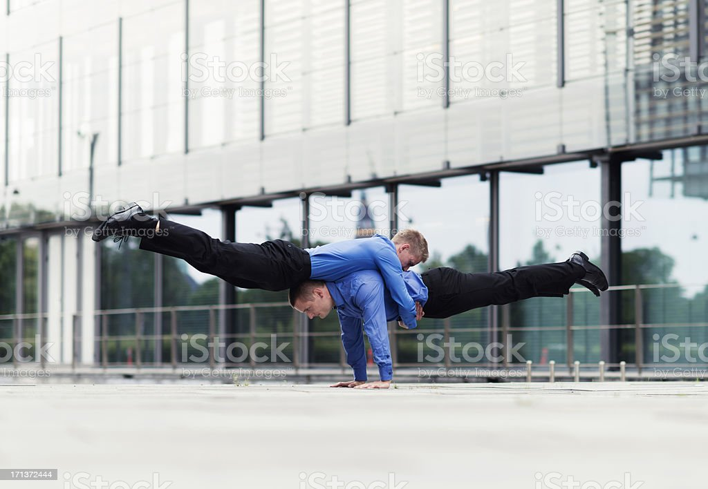 Teamwork by two very acrobatic businessmen royalty-free stock photo