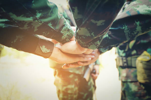 teamwork concept : group of soldier hands together cross processing ready to fight. - armed forces stock photos and pictures