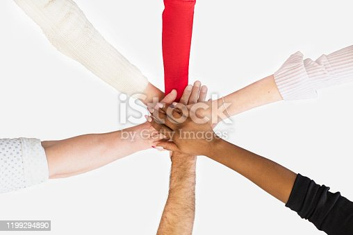 A multi-ethnic group of coworkers joining hands in the center of a circle during a meeting as a sign of teamwork.